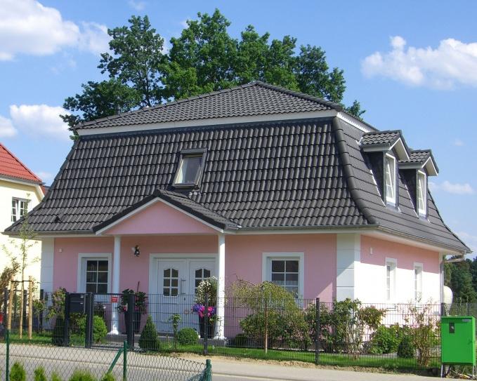 Дом с розовым фасадом.  Нежно-розовый оттенок фасада выделяет этот дом среди остальных построек.